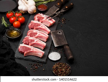 Fresh raw butchers lamb beef cutlets on stone board with vintage meat fork and knife and hatchet on black background.Salt, pepper and oil with tomatoes and garlic and barbecue sauce.