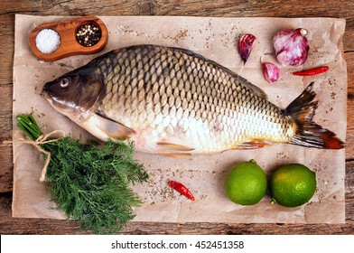 Fresh raw carp fish with lime, dill and garlic on old wooden background.