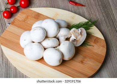 Fresh raw Champignons on the wood background served green dill