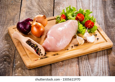 Fresh raw chicken fillet on wooden cutting board on wooden table