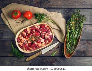 Fresh raw chicken hearts in a ceramic bowl. Seasonings for chicken hearts, thyme, rosemary, parsley, pepper, tomatoes. Rustic wooden gray background. Top view.