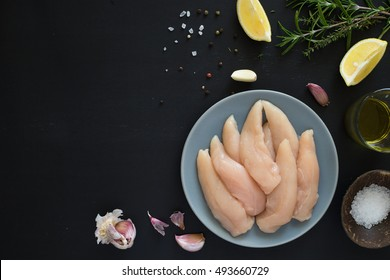 Fresh raw chicken tenders, lemon, garlic, rosemary, olive oil, pepper and salt on dark background