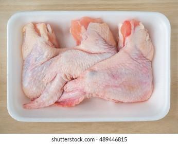 Fresh raw chicken wings on foam plate