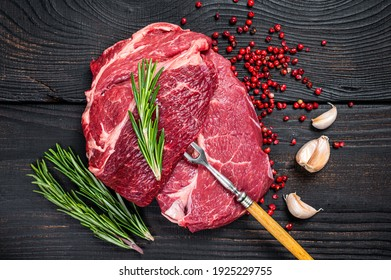 Fresh Raw Chuck eye roll beef steak on butcher table. Black wooden background. Top view