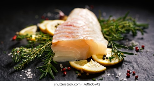 Fresh raw cod fillet with addition of herbs and lemon slices on black stone background