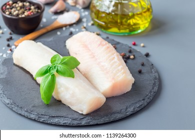 Fresh raw cod fillet with spices, pepper, salt, basil on a stone plate, horizontal, copy space