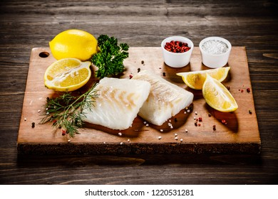 Fresh raw cod with herbs served on cutting board on wooden table