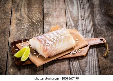 Frischer roher Kabeljau mit Zitrone auf Holztisch