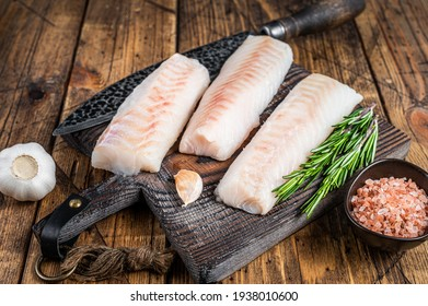 Fresh Raw cod loin fillet steaks on wooden board with butcher knife. wooden background. Top view