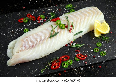 Fresh Raw Cod loin fillet with rosemary, chillies, cracked pepper and lemon on stone board