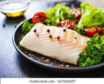 Fresh raw cod with vegetables on black stone board