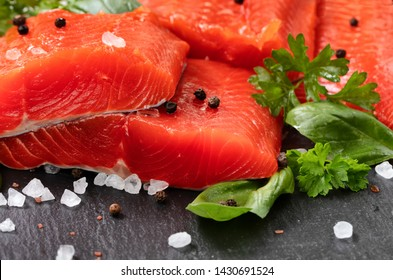 Fresh raw copper river sockeye salmon fillets on natural stone with herbs and seasoning
