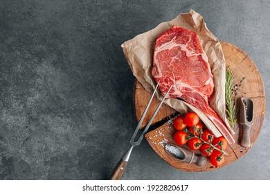 fresh raw cowboy tomahawk steak on a round wooden cutting board for meat