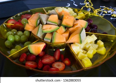 Fresh Raw Cube Cut Pineapples, Sliced Cantaloupe Honeydew Melon on a Sectioned Party Fruit Platter Tray next to Purple Grapes, Green Grapes and Red Strawberries