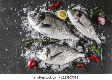 Fresh raw dorado fishes with spices, lemon, pepper, rosemary on ice over dark stone background. Creative layout made of fish, top view, flat lay