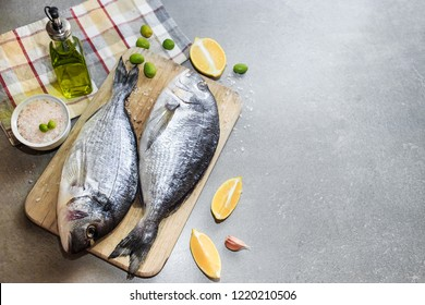 Fresh raw dorado or sea bream fish on a wooden kitchen board with lemon slices, spices, Himalayan pink salt, olive oil. Gray background. Mediterranean Kitchen. Top view. Place for text.