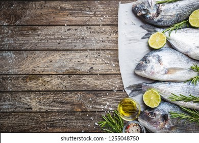 Fresh raw Dorado or sea bream with spices, herbs, lemon and salt over wooden background Top view