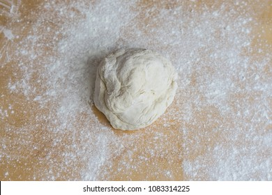 Fresh raw dough for pizza or bread baking on grey background, Risen or proved yeast dough for bread or pizza on a floured slate surface, Ball of dough with dusting of flour
