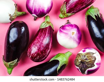 Fresh raw eggplants of different color and variety on a pink background, top view, copy space