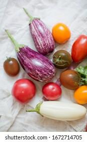 Fresh raw eggplants, tomatoes and parsley on a vintage napkin