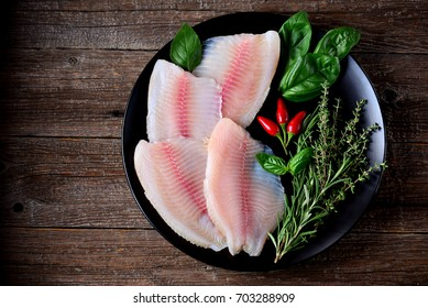 Fresh raw fillet of tilapia fish with thyme, rosemary, basil and chili pepper. Top view. Copy space.