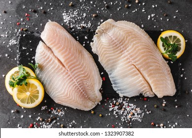 Fresh raw fillet white fish Pangasius with spices and lemon on dark stone background.  Seafood, top view, flat lay, copy space