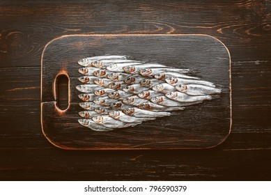 fresh raw fish anchovy and sprat on a wooden surface