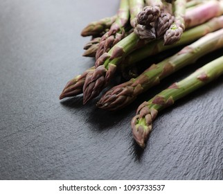 Fresh raw green asparagus on a black stone background. Asparagus season. Close up. Selective focus