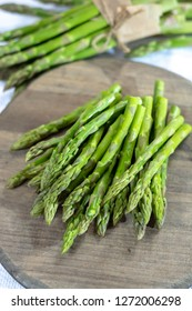 Fresh raw green asparagus vegetable on wooden plank close up