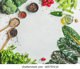 Fresh raw greens, vegetables, olive oil and grains over light grey marble kitchen countertop, top view, copy space. Healthy, clean eating, vegan, vegetarian, detox, dieting food concept