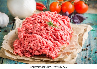 fresh raw ground beef on a paper on a rustic wooden table