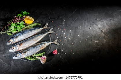 Fresh raw herrings with herbs, spices, onion and parsley on dark background. Top view with copy space