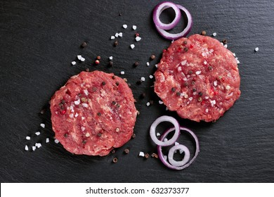 Fresh raw home-made minced beef steak burger with spices and onion, on a black slate table, copy space, top view