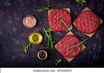 Fresh raw homemade minced beef steak burger with spices on black background. Flat lay. Top view