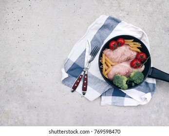 Fresh raw ingredients for cooking one pot chicken with broccoli pasta penne and cherry tomatoes. Raw chicken fillet with vegetables. Healthy clean eating. Top view. Space for text.