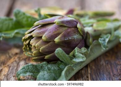 Fresh raw italian artichokes on wooden background