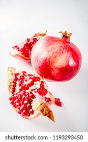 Fresh raw juicy whole and broken pomegranate on white background, top view flatlay creative layout
