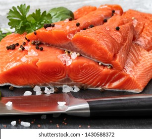Fresh raw king salmon fillets on natural stone with herbs and seasoning