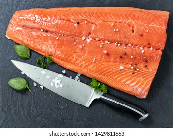 Fresh raw king salmon on natural stone with herbs and seasoning