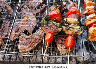 fresh raw lamb ribs on meat holder over fire burned churcoal with vegetable shish kebab on side outdoor party