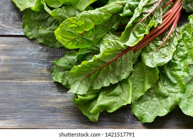 Fresh raw leaves of chard, leaf beets, mangold, swiss chard on a wooden table, close up, free space