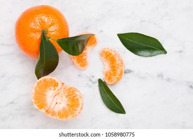 Fresh raw mandarin tangerine fruit with leaves on marble background