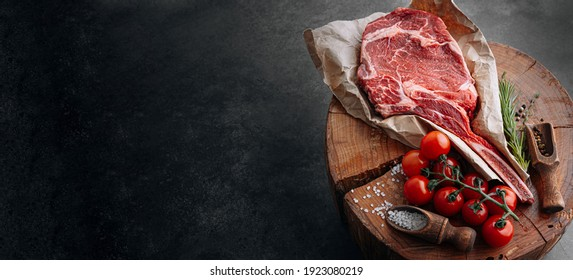 fresh raw marbled beef steak with ingredients rosemary thyme cherry tomatoes pepper salt on a wooden table with a meat ax