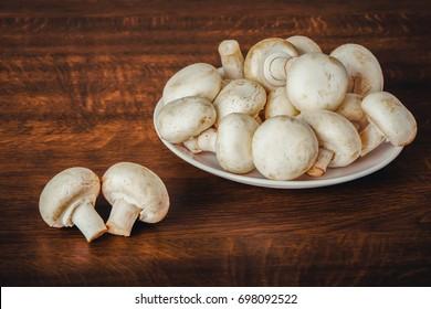 Fresh raw mashroom lying on a plate.