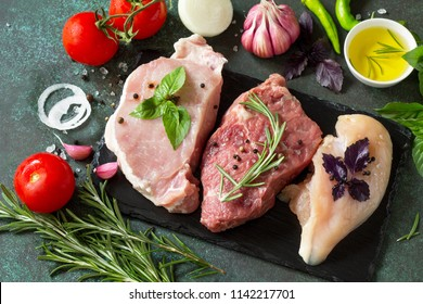 Fresh raw meat. Different types of raw pork meat, chicken fillet and beef with vegetables and herbs on dark wooden background.
