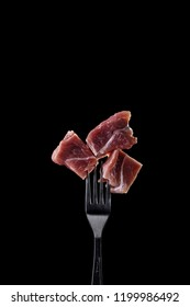 Fresh and raw meat on a fork on black background.