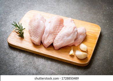 fresh raw middle chicken wings on wooden board with ingredients - Shutterstock ID 1728850489