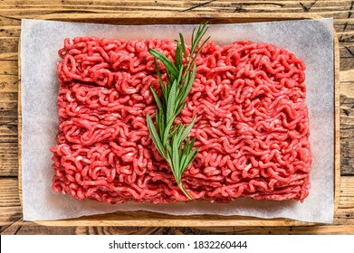 Fresh Raw mince beef, ground meat on butcher paper. wooden background. Top view - Shutterstock ID 1832260444