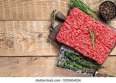 Fresh Raw mince beef meat on a butcher cutting board with cleaver. Wooden background. Top view. Copy space - Shutterstock ID 1920454334