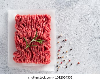 Fresh raw minced beef on backing paper over light gray cement background with copy space. Top view or flat-lay.